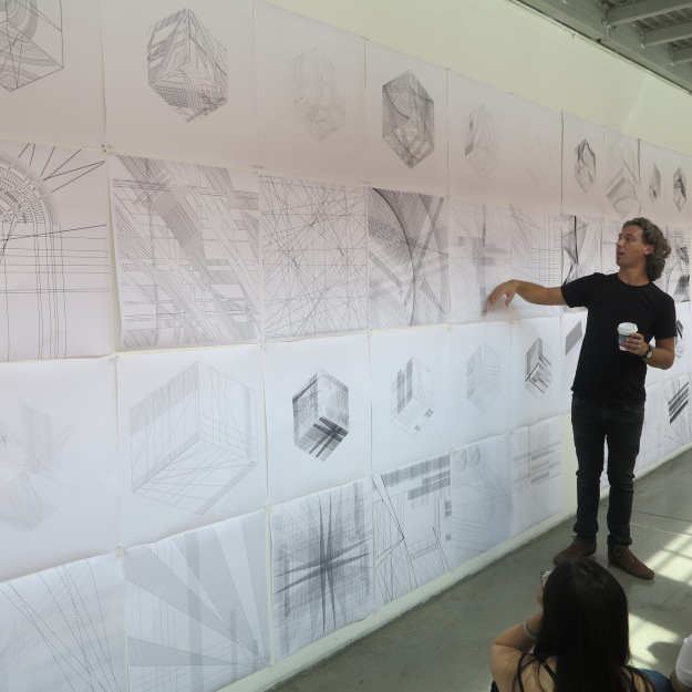 Professor Alexis Rochas critiques student work during a Making + Meaning class session.