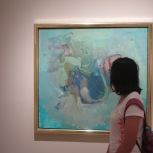 A student observes a painting at LACMA.